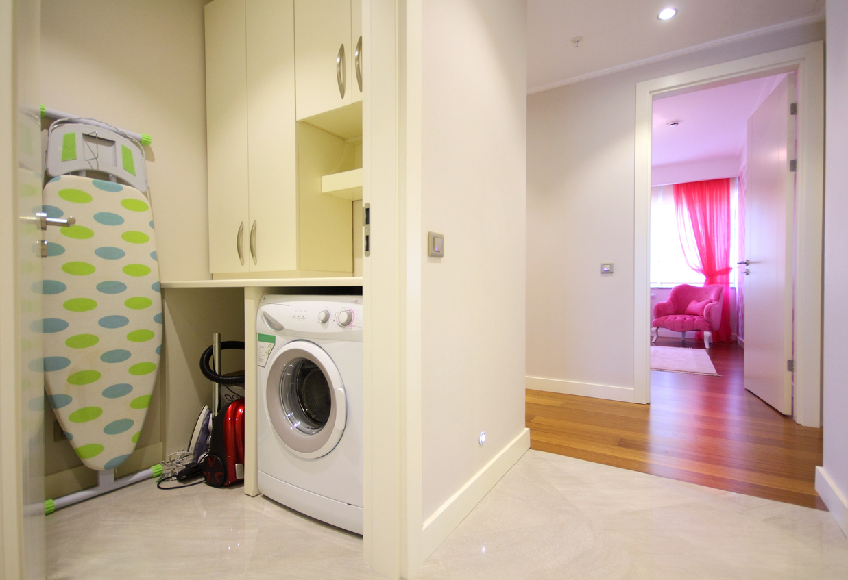 A small laundry room with shelves