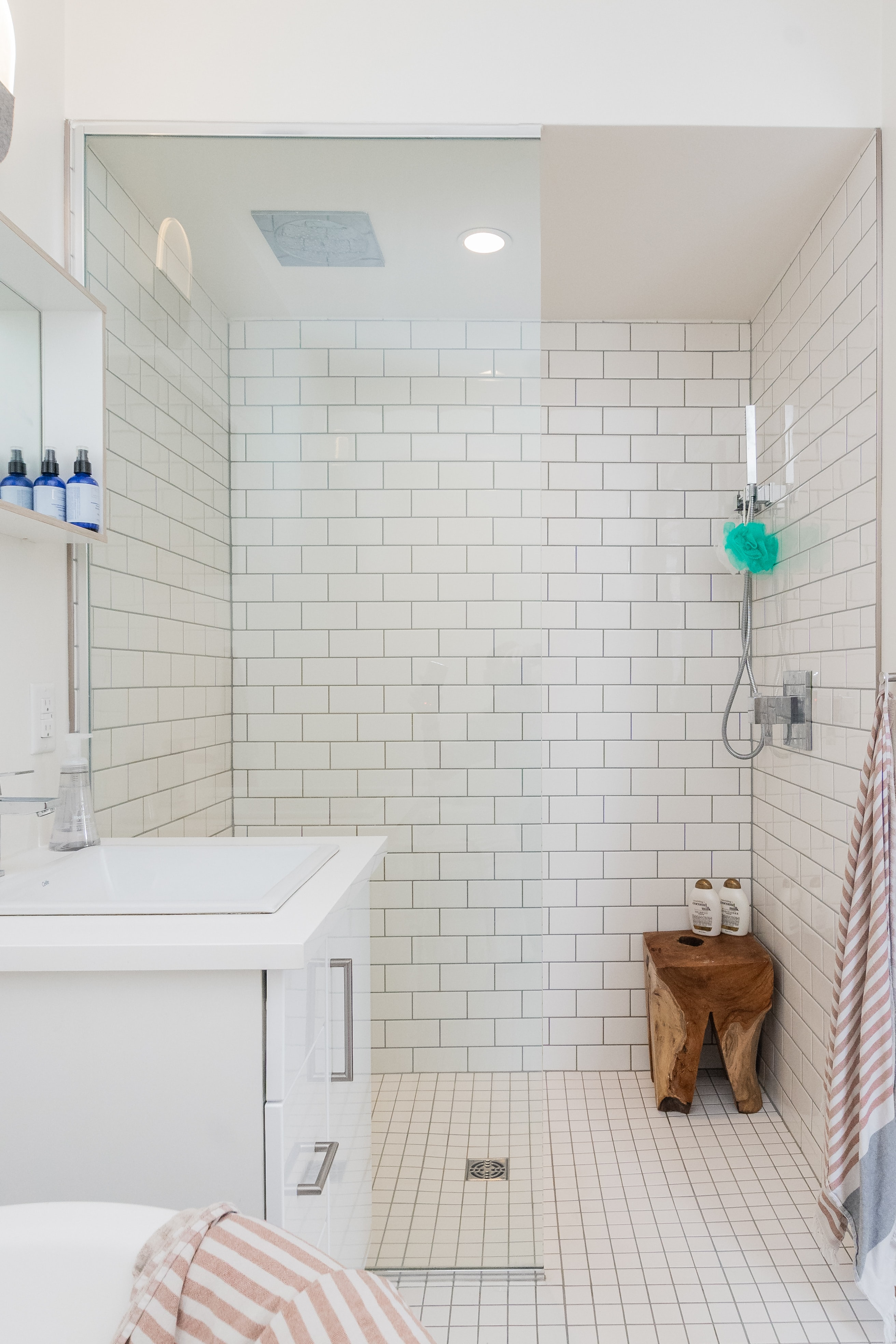 A small bathroom with wooden step stool.