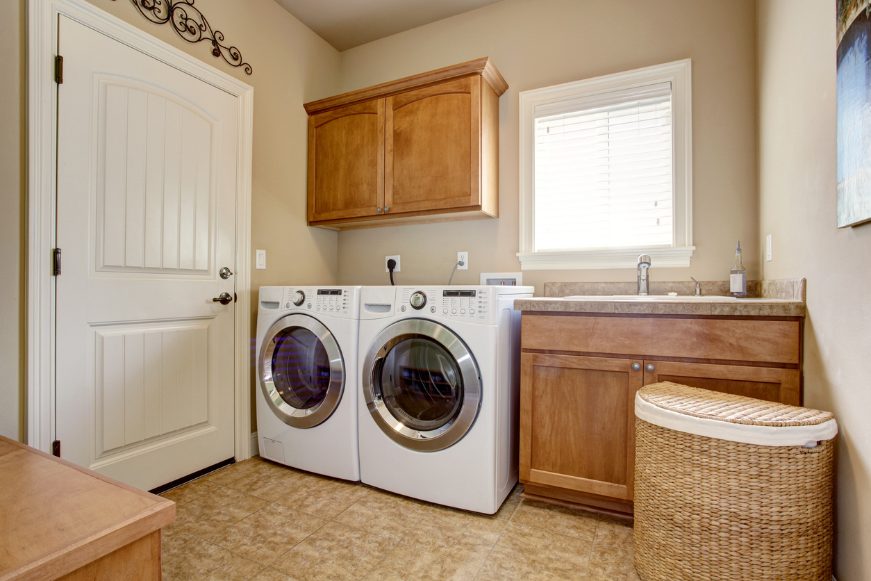A medium laundry room with cabinets