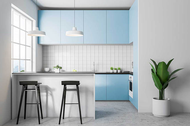 A small kitchen with light blue, slab-style cabinets.