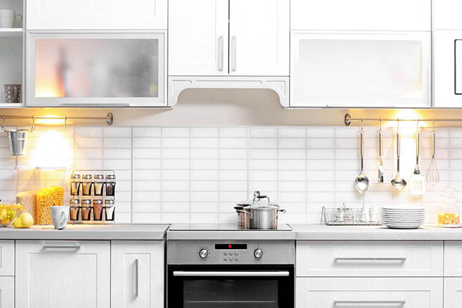A large kitchen with bright white cabinets and stainless steel appliances.