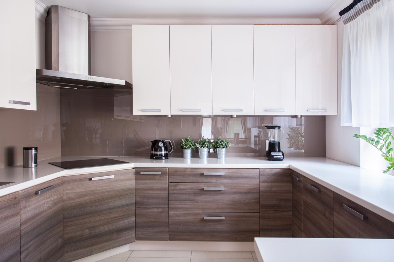 A small, modern kitchen with slab-style thermofoil cabinets.