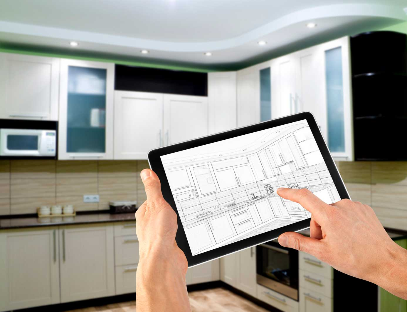 man reviewing designs for kitchen on his tablet